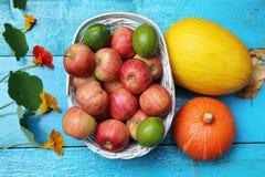 Früchte im Weidenkorb auf der hölzernen blauen Tabelle Stockfoto