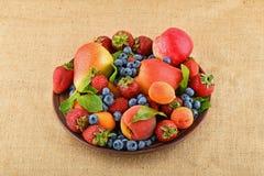 Früchte und Beeren mischen in der keramischen Platte auf Leinwandsegeltuch Stockfoto