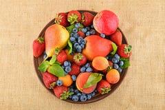 Früchte und Beeren mischen in der keramischen Platte auf Leinwandsegeltuch Stockfotografie