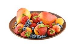 Früchte und Beeren mischen in der keramischen Platte, die auf Weiß lokalisiert wird Lizenzfreies Stockbild