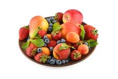 Früchte und Beeren mischen in der keramischen Platte, die auf Weiß lokalisiert wird Stockfoto