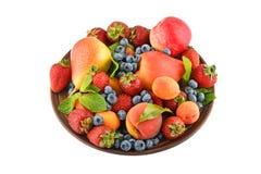 Früchte und Beeren mischen in der keramischen Platte, die auf Weiß lokalisiert wird Lizenzfreies Stockfoto