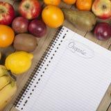 Früchte und Buch auf hölzerner Oberfläche Lizenzfreie Stockfotos