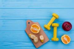 Früchte und Dummköpfe auf Farbhölzernem Hintergrund lizenzfreie stockbilder