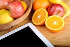 Früchte und ein Tablet-PC auf Holztisch stockbilder