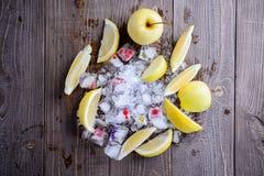 Früchte und Eis auf einem hölzernen Hintergrund Stockfotografie