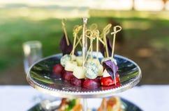 Früchte und Käse der blauen Trauben auf Aufsteckspindeln für Aufschlag auf Teller im Hochzeitsfest Stockbilder