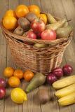 Früchte und Korb auf hölzerner Oberfläche Lizenzfreie Stockfotos