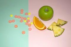 Früchte und Pillen auf einem blauen und rosa Hintergrund Gesundheit und natürliche Vitamine Stockfotografie