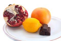 Früchte und Süßigkeiten auf Platte lizenzfreie stockbilder