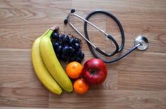 Früchte und Stethoskop auf dem hölzernen Hintergrund Lizenzfreie Stockfotografie