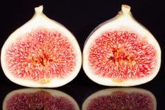Früchte von unterteilten frischen Feigen auf schwarzem Hintergrund Stockfotografie