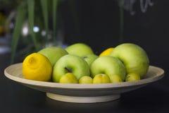 Früchte - Zitronen, grüne Äpfel und gelbe Pflaumen auf einer Servierplatte auf a Lizenzfreie Stockbilder