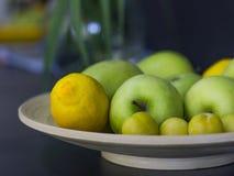 Früchte - Zitronen, grüne Äpfel und gelbe Pflaumen auf einer Servierplatte auf a Lizenzfreies Stockbild