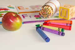 Frühe Kindheit, die mit Buch und Zeichenstiften lernt Stockbild