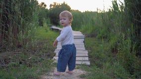 Frühe Kindheit, froher Säuglingsjunge, der barfuß auf Holzbrücke in Natur unter dem grünen Gras geht stock video
