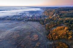 Früher kalter Morgen Nebel und Frost Kleinstadtdorf umgeben durch Hügel und Ebene Luftbrummenfoto lizenzfreie stockfotografie