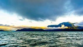 Früher Morgen-Sonnenaufgang und dunkle Wolken über Harrison Lake Stockfotos