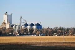 Früher Wintermorgen auf landwirtschaftlichem Ackerland und Silos Lizenzfreies Stockfoto