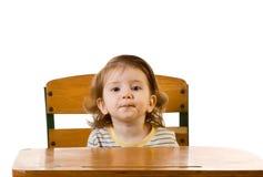 Frühes Ausbildungs-Baby, das am Schuleschreibtisch sitzt stockfotografie