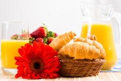 Frühes Frühstück, Saft, Hörnchen und Beeren Stockfoto