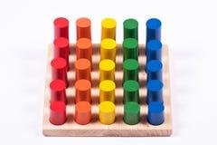Frühes Lernenspielzeug: Zylinder von verschiedenen Farben und von Höhe Stockfoto