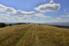 Frühherbstlandschaft mit Hügeln und Landstraße Lizenzfreie Stockfotografie
