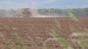 Am Frühjahr ein Traktor, der an dem Ackerland arbeitet stock footage