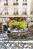 Frühjahr mit roten Pelargonien auf einem Balkon in Paris, Frankreich lizenzfreie stockbilder