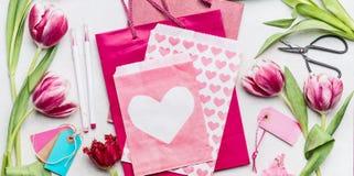 Frühjahrarbeitsplatz mit Tulpenblumen, Scheren, rosa Papiertüten und Umschlag mit Herzen, Draufsicht, Kopienraum Geschenk und Gru Stockfoto