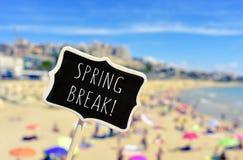 Frühjahrsferien in einem schwarzen Schild auf dem Strand Lizenzfreies Stockbild