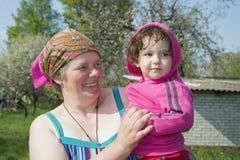 Frühling in der Gartengroßmutter hält die kleine großartige Tochter Stockfotografie