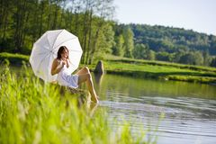 Frühling - glückliche romantische Frau, die durch See sitzt lizenzfreie stockfotos