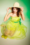 Frühling oder Sommer. Mädchen der jungen Frau im Hut und im grünen Kleidersitzen Stockfotos
