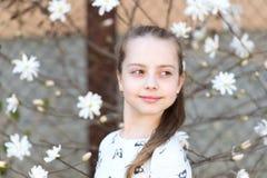 Frühlings-, Ostern- und Feiertagsfeierkonzept Kleines Mädchen auf Blumenblüte im Frühjahr Kind mit den blühenden Blumen im Freien Stockfoto