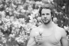 Frühlings-Saison-Konzept Neues Leben und Optimismus Macho mit Bart im grauen Unterhemd auf Blumenhintergrund lizenzfreie stockbilder