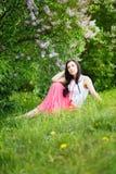 Frühlings-Schönheits-Mädchen. Schöne junge Frau, die auf Grün sitzt Lizenzfreie Stockfotos