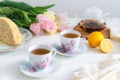 Frühlings-Teeparty mit selbst gemachtem Kuchen, Zitrone, Teekanne und Tulpen auf dem Hintergrund Kopieren Sie Platz Mutter ` s Ta lizenzfreie stockbilder