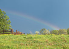Frühlingsbauernhofweide mit Regenbogen Stockbild