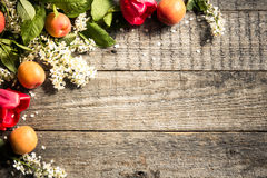 Frühlingsblumen, Aprikosen auf hölzernem Hintergrund Lizenzfreie Stockfotografie