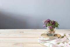 Frühlingsblumen und weißes Tuch auf dem hölzernen Schreibtisch stockbilder