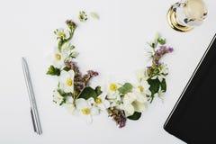 Frühlingsblumen zeichneten in Form eines Halbmonds mit einem Notizblock Lizenzfreie Stockfotografie