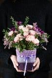 Frühlingsblumenstrauß in den Töpfen in den Händen eines Mädchens stockbilder