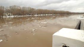 Frühlingsfluß mit schmutzigem braunem Wasser und Eis Schwimmen des Eises stock footage