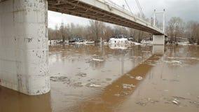 Frühlingsfluß mit schmutzigem braunem Wasser und Eis Schwimmen des Eises und der Brücke stock video