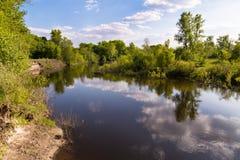 Frühlingsflusslandschaft auf Hintergrund von grünen Bäumen und von Wolken Stockfotos