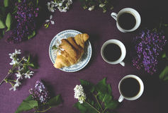 Frühlingsfrühstück: Kaffee, Hörnchen und Blumen Stockbild