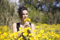 Frühlingsfrau mit gelben Blumen Lizenzfreie Stockfotografie