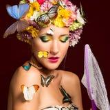 Frühlingsfrau mit Schmetterlingen und Blumen Stockbilder