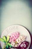 Frühlingsgedeck mit Platte, Band und reizenden Hyazinthen blüht, Draufsicht, Grenze, Pastellfarbe stockfotografie